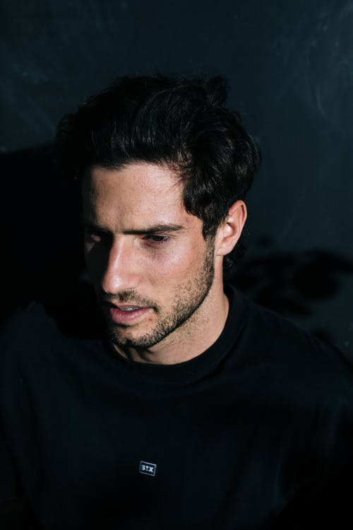From above side view of pensive male with beard and dark hair looking away while standing on black background in bright sunshine