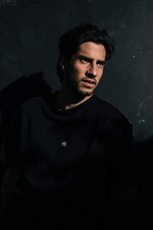 Contemplative man with mustache in black apparel