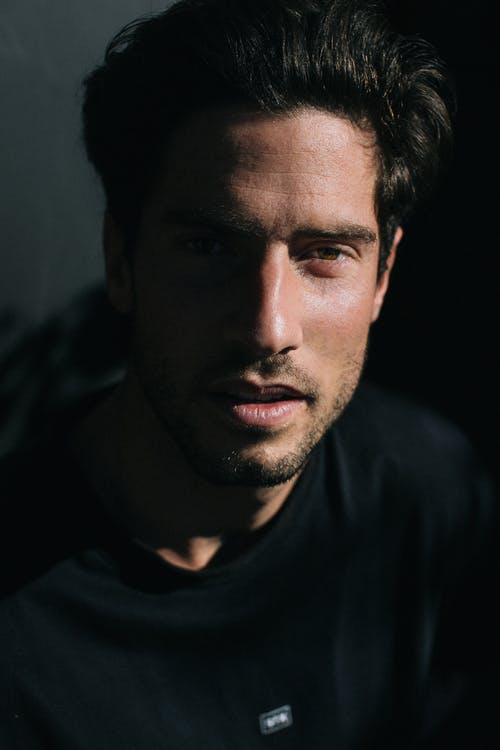 Serious masculine male with beard and modern haircut looking at camera on dark background