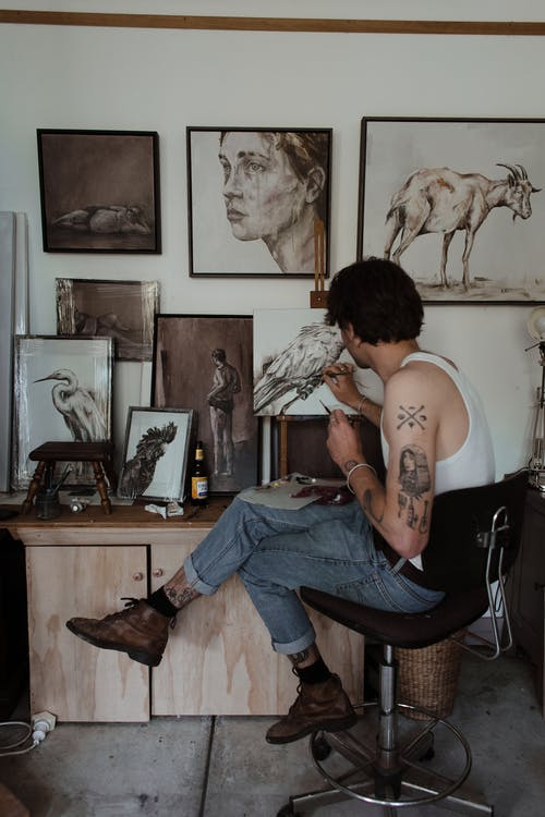 Unrecognizable man painting in creative workshop