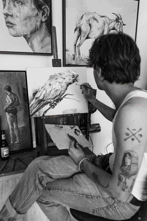 Side view of black and white young tattooed male sitting on chair and drawing various pictures with paintbrush in creative studio