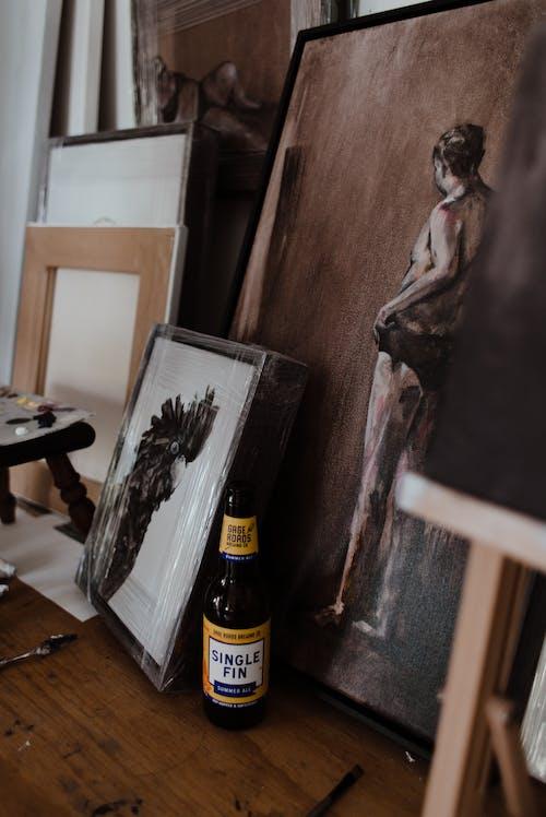 Various framed paintings arranged on table in workshop