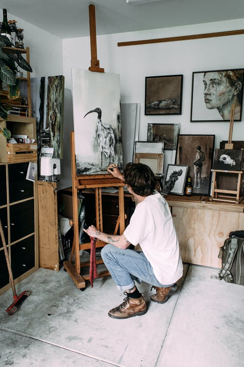Side view of unrecognizable focused young male painter in stylish clothes sitting on haunches while drawing on easel in creative art studio