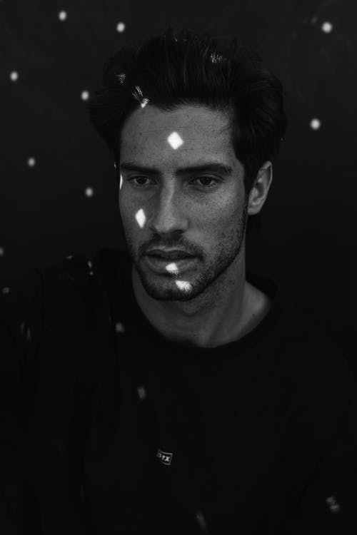 Black and white of calm young Hispanic male model with light spots on face in casual clothes looking away pensively in dark studio