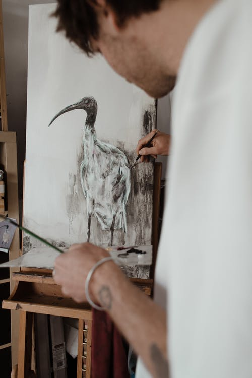 Crop concentrated young male painter drawing bird on easel in workshop