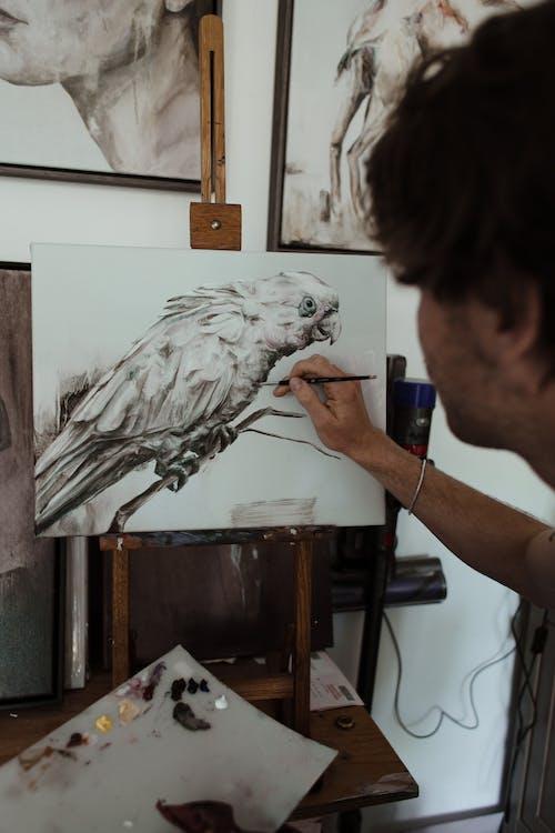 Unrecognizable artist painting parrot in workshop