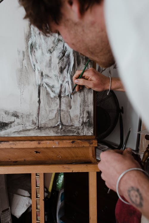 Crop unshaven young male artist drawing on canvas fixed on easel with pencil in traditional workshop