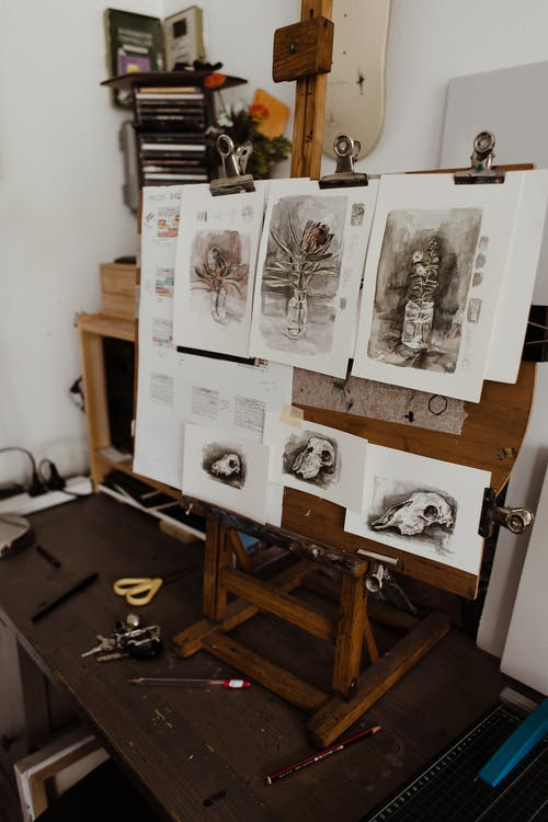 Assorted paintings attached to easel in workshop