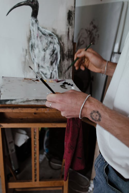 Crop faceless male artist with tattoo on hand in casual clothes standing near easel while painting ibis bird with paintbrush in workshop
