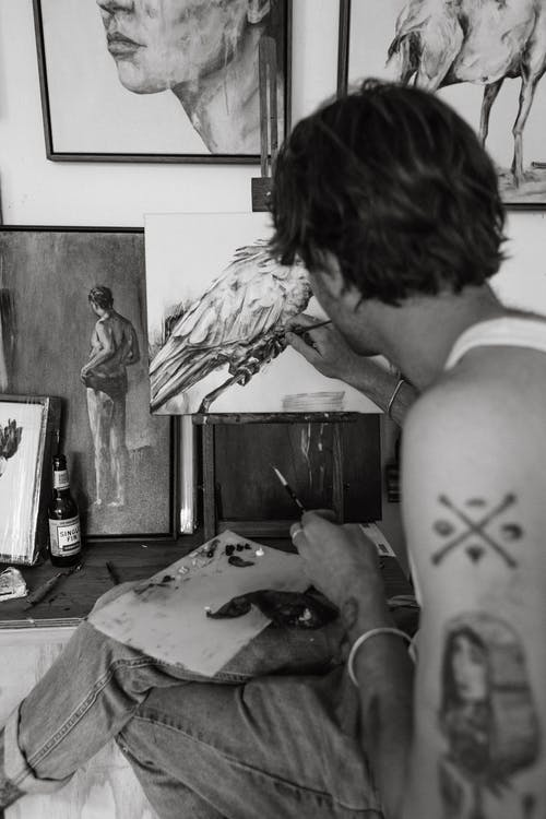 Calm young tattooed guy drawing picture in art studio