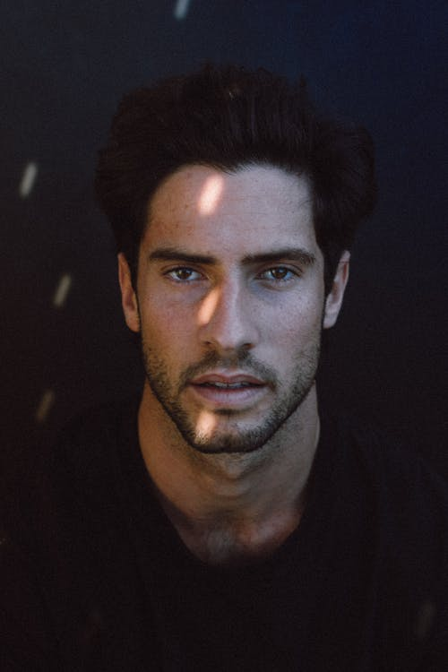 Handsome young pensive Hispanic male model with dark hair in casual clothes looking at camera with concentration in black studio with sun flares