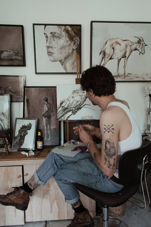 Side view of unrecognizable trendy tattooed male painter in casual outfit sitting on chair and mixing inks while drawing in creative workshop