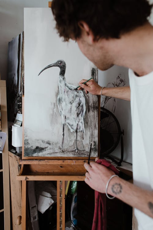 Crop artist painting picture in workshop