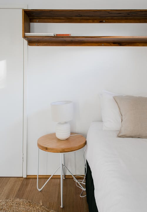 Round wooden bedside table with lamp placed near comfortable bed with cushions at white wall with shelves in light bedroom