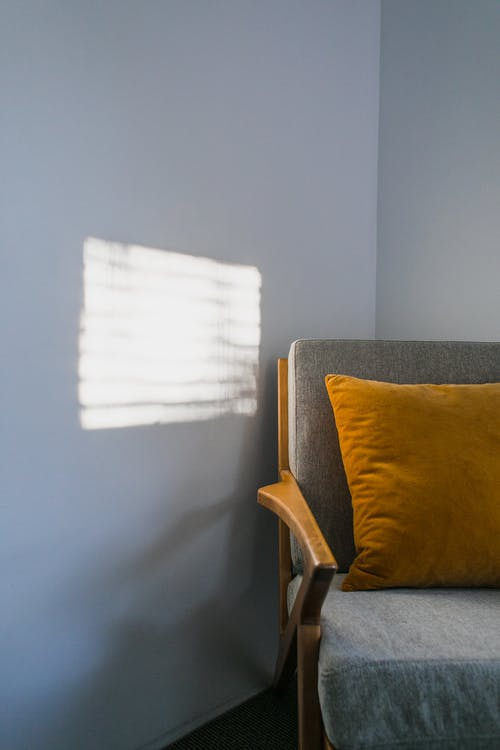 Comfortable gray armchair with orange pillow placed in corner of light room with bright sunlight on white wall at home