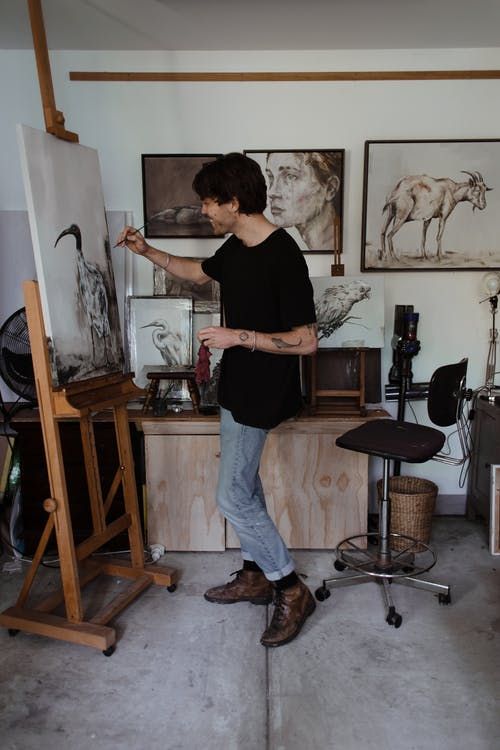 Man painting on easel in workshop
