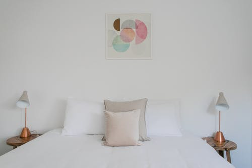 Comfortable bed with cushions and white sheets placed between lamps at white wall with creative painting in light bedroom at home