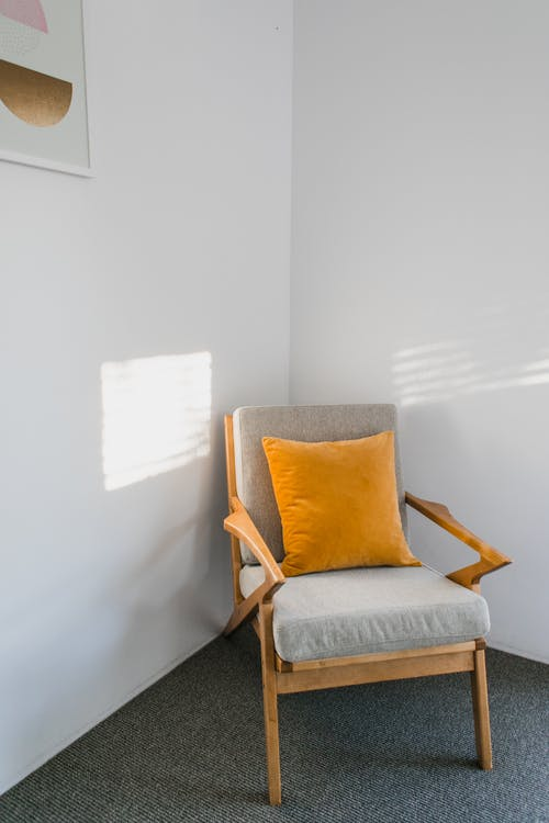 Comfortable wooden gray armchair with orange pillow placed near white wall with picture in light room with sunlight at home
