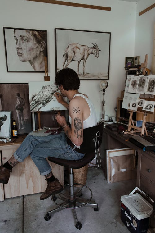 Skilled man drawing on canvas