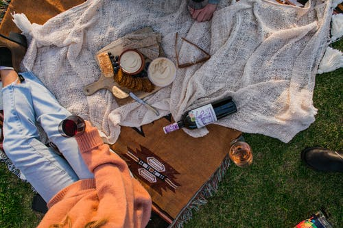 Top view of anonymous female with glass of wine sitting on plaid with food while having picnic on grassy lawn