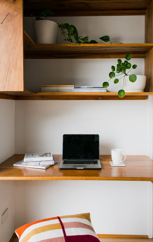 Modern netbook with black screen on wooden table with cup of hot drink near shelves with potted flowers at home