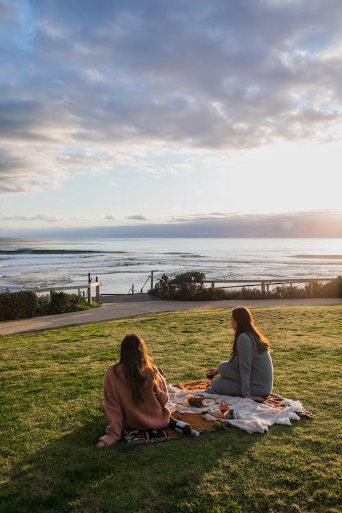 Unrecognizable women having picnic on grassy coast