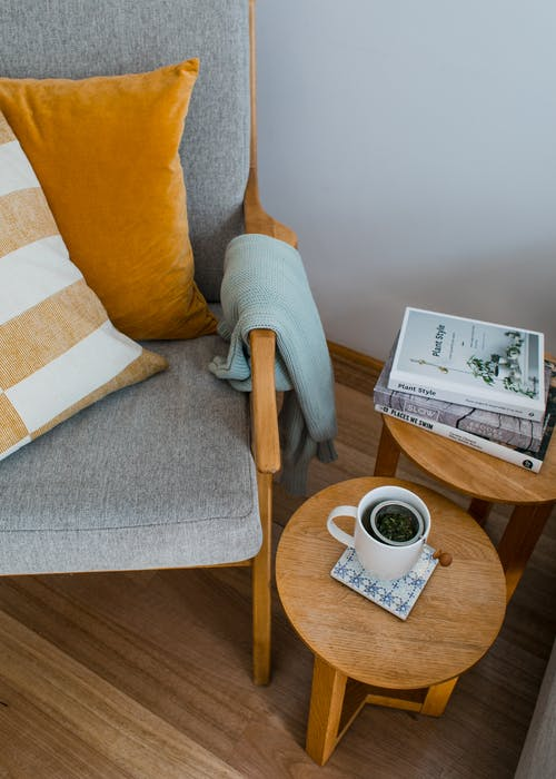 From above of comfortable armchair with colorful pillows placed near wooden side tables with books and cup of tea in living room