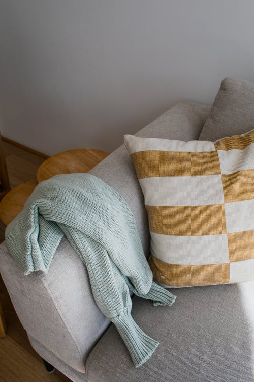 From above of comfortable gray couch decorated with pillow near sweater in lounge