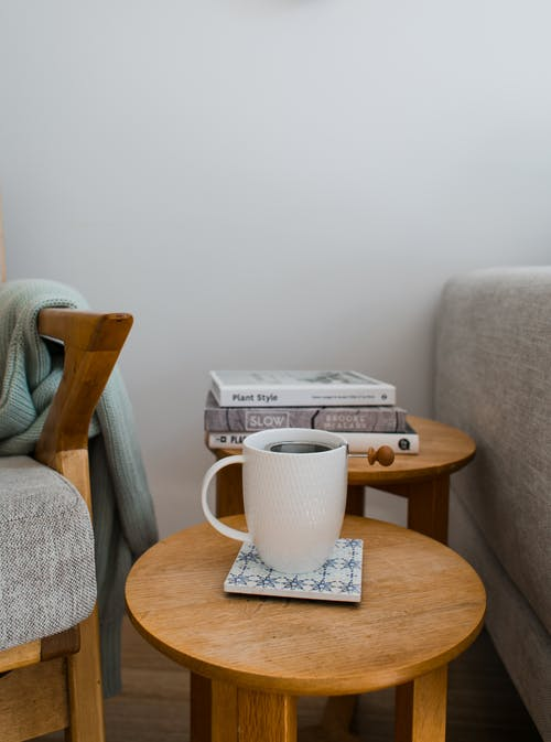 Mug of delicious aromatic hot coffee on timber table composed near books and soft cozy armchairs