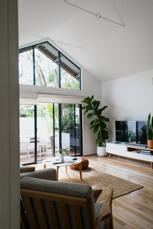 Interior of contemporary cozy living room with modern TV and soft armchairs in daylight