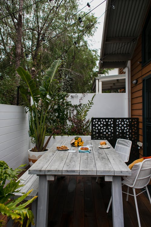 Wooden table with chairs places on terrace of residential house in countryside in daytime