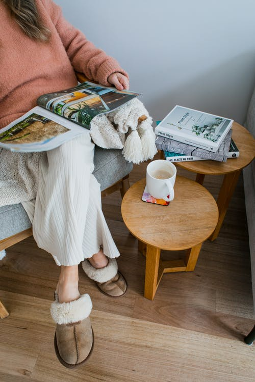 Anonymous lady in armchair reading magazine near table with cup