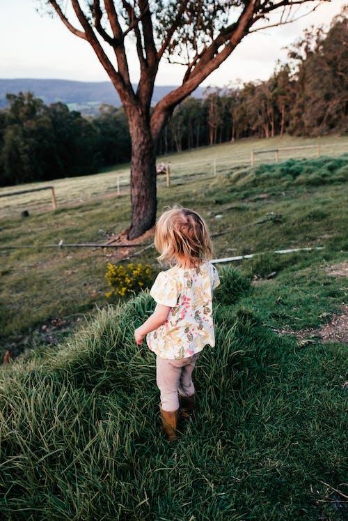 Faceless girl standing on lush grassy glade