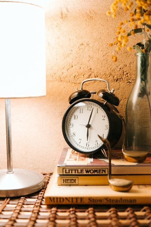 Vintage alarm clock and luminous lamp placed on bedside table