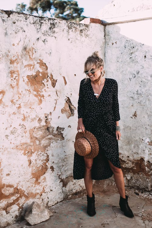Full body cheerful laughing young female in trendy black dress standing near shabby weathered wall on sunny day