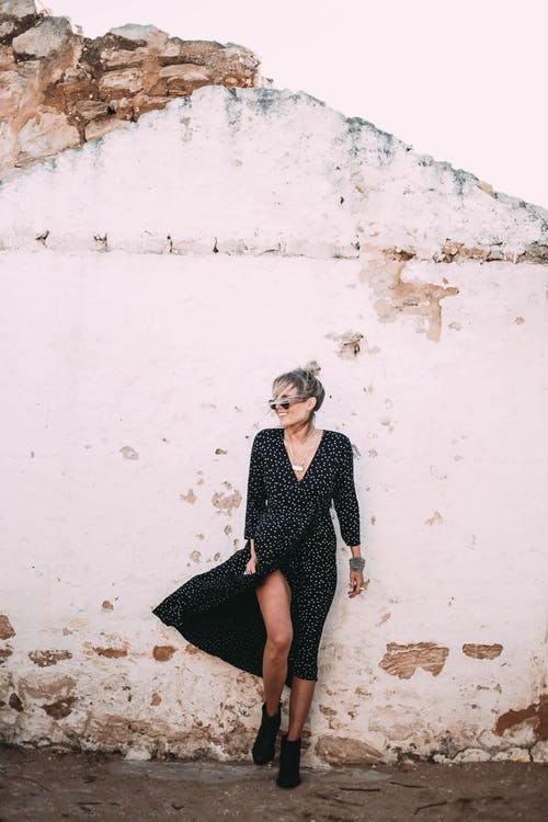 Full length young attractive female wearing trendy black dress and sunglasses standing against weathered remaining wall of ruined abandoned building and looking away