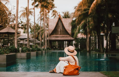 Anonymous female relaxing near calm rippling water of pond surrounded with houses and palm trees