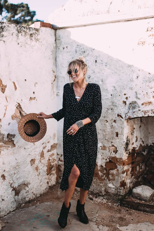 Stylish woman in trendy dress near weathered concrete building