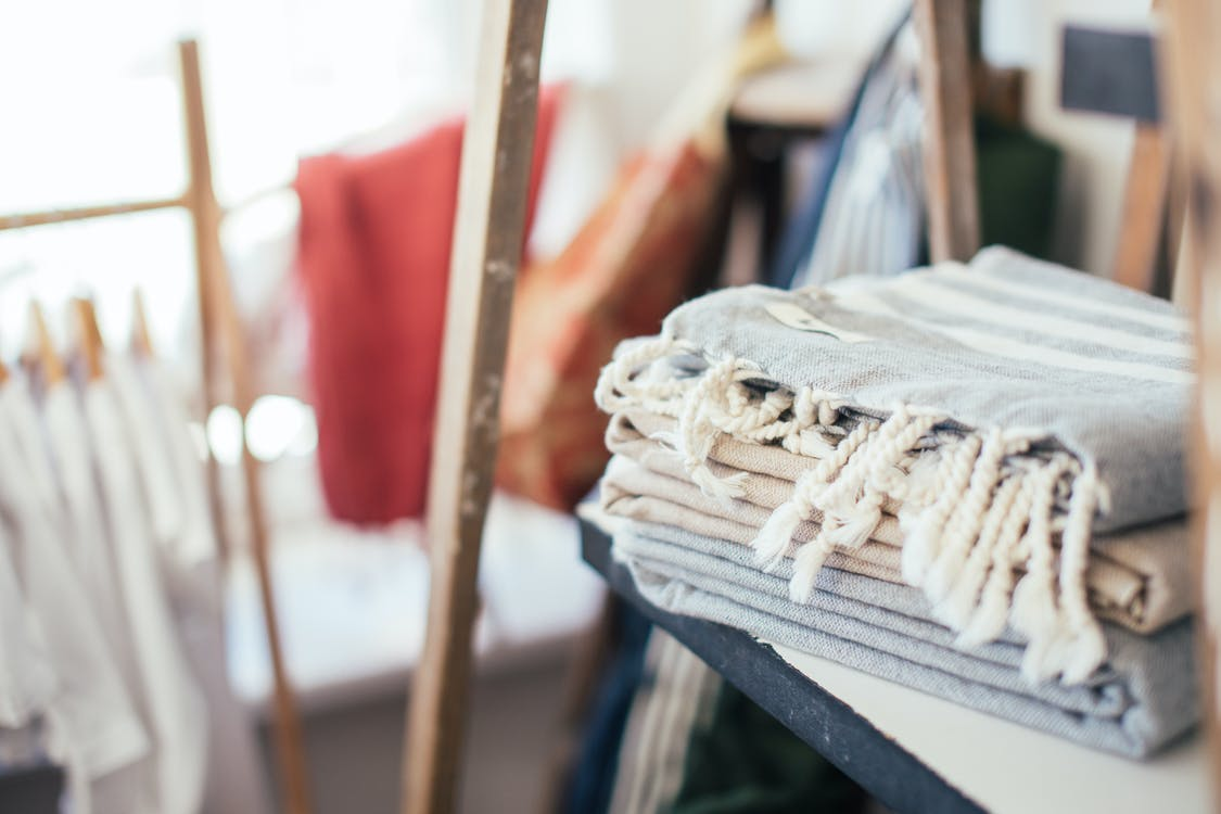 Towels placed on shelf near clothes hanging on rope