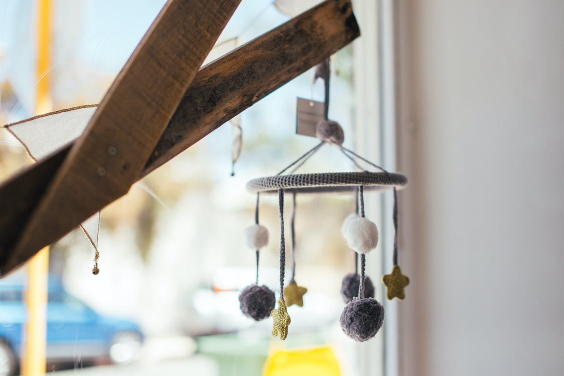 Soft baby mobile hanging on wooden planks near window at home in daytime