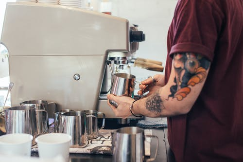 Crop anonymous male with tattoos preparing tasty aromatic coffee with coffee machine and pitcher