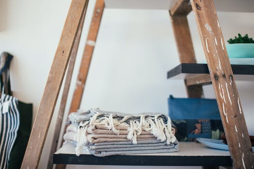 Stack of clean cotton towels with tassels placed on shelf at home in daytime