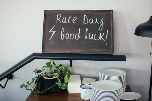 Stack of clean plates and cup near green potted plant under signboard wishing luck in race
