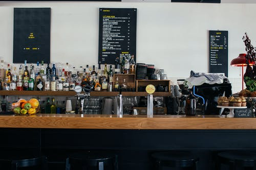 Contemporary cafe with wooden shelves full of many bottles and menu on wall