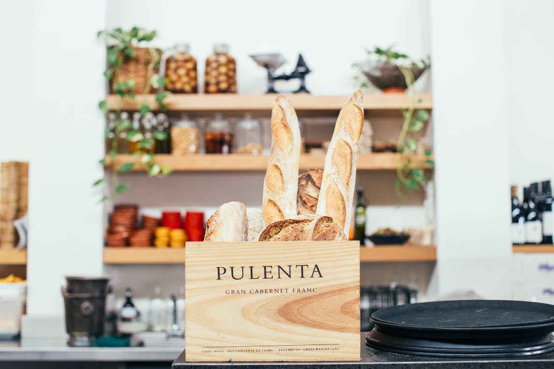 Tasty fragrant baguettes and bread placed in timber box on counter of modern cafe on blurred background