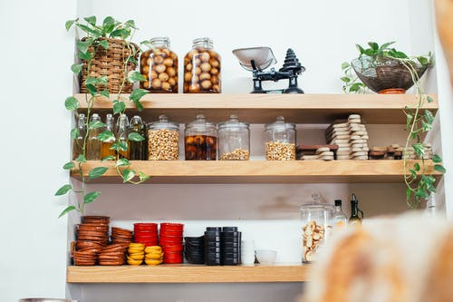 Timber shelves with many glass jars filled with nuts near green potted plants and plastic containers