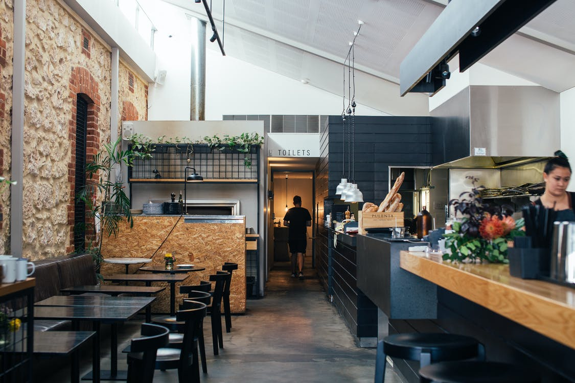 Contemporary restaurant with comfortable interior with chairs and tables near counter in daytime