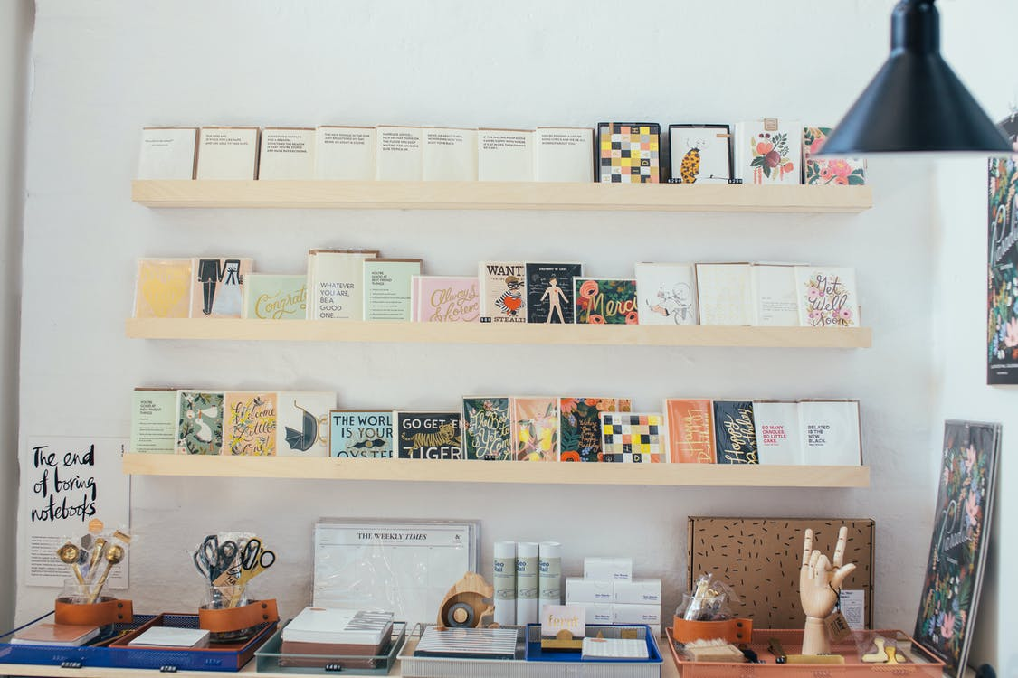 Interior of modern light shop with wooden shelves with various books and stationery composed with creative decorative elements