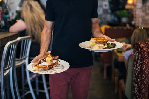 Crop faceless waiter holding plates with appetizing sandwiches in with toasted bread in modern restaurant during lunch