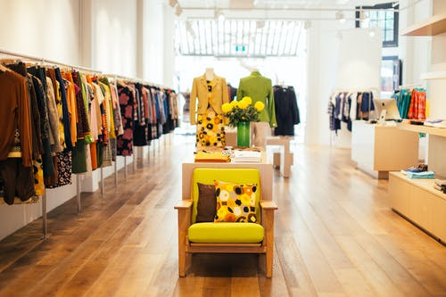 Interior of modern fashion store with stylish colorful clothes handing on rack in daytime